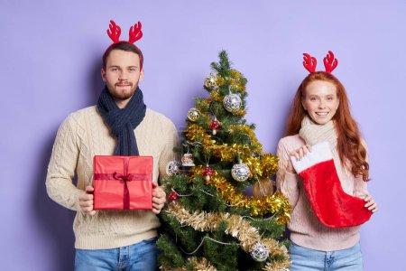 Photo pour Doux beau couple debout près décoré beau sapin de Noël, portant des cornes rouges drôles, regardant la caméra avec des visages calmes et agréables, tenant cadeau de Noël et chaussette Santas dans les mains - image libre de droit