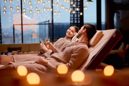 Liebendes kaukasisches junges Paar trinkt Champagner liegend in einem Wellnesszentrum
