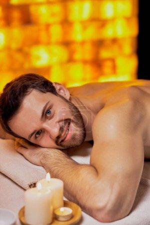 Photo pour Portrait d'un jeune homme caucasien allongé sur une table de massage au spa avec peau nue, massage sur le dos et les épaules. Sourire et regarder la caméra, s'amuser des procédures de spa - image libre de droit