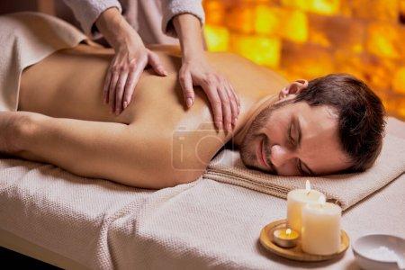 Photo pour Un jeune homme caucasien se détend pendant un massage sur le dos fait par une femme allongée sur la table du spa. - image libre de droit