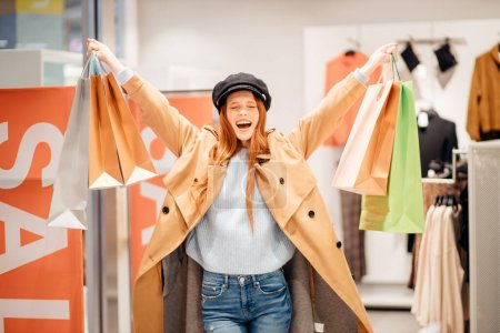 Photo pour Joyeuse femme souriante positive aux cheveux roux heureux après les achats, les mains levées tenant des sacs à provisions en papier . - image libre de droit