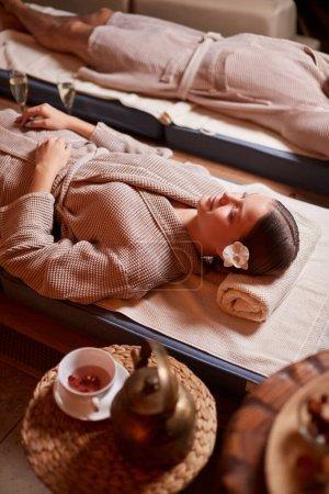 Photo pour Jeune homme et femme caucasien portant un peignoir, couché et en train de se ressourcer au spa du salon de beauté. Concept de détente et de mode de vie sain - image libre de droit