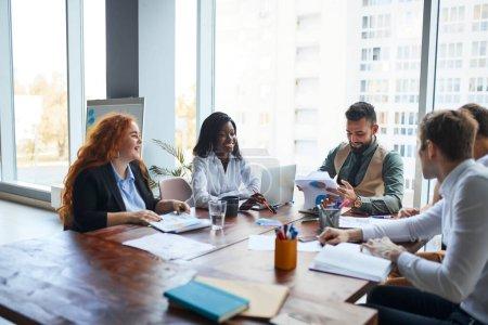 Photo pour Une équipe multiethnique de collègues qui organisent une séance de remue-méninges autour d'une table avec des ordinateurs portables dans le bureau alors qu'ils planifient leur stratégie commerciale pour le travail futur. Concept de gens d'affaires - image libre de droit