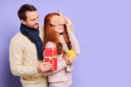 Photo pour Amour doux mari essayant d'impressionner jolie femme mignonne avec cadeau de Noël, debout derrière, mettant la main sur les yeux féminins, exprimant l'intérêt, heureux de faire un cadeau agréable pour petite amie - image libre de droit