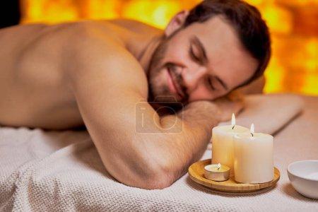 Photo pour Jeune homme d'apparence caucasienne allongé sur une table de spa, se détendre et méditer - image libre de droit