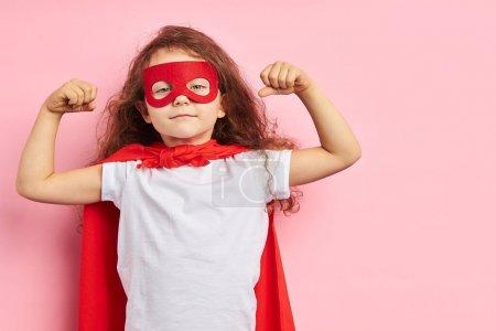 Photo pour Petite fille séduisante vêtue d'un costume et d'un masque de héros rouge montrant comment elle est forte isolée sur fond rose - image libre de droit
