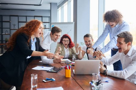 Photo for Everyday winners. Cheerful group of happy business people in formal wear looking at the laptop and gesturing, celebrate winning - Royalty Free Image