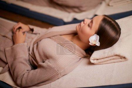 Photo pour Une femme séduisante prend plaisir à passer du temps dans un salon de spa allongé sur le lit dans un peignoir et à suivre des procédures thermales. repos et confort. - image libre de droit