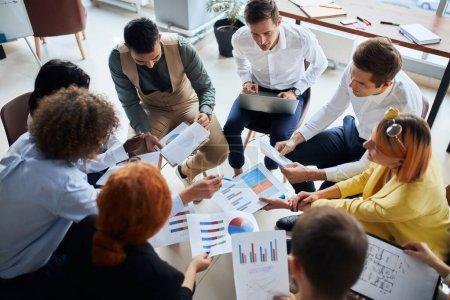 Photo pour Divers jeunes d'une équipe d'affaires se sont réunis pour discuter de la création d'entreprise dans un bureau moderne, assis ensemble en cercles tenant des documents avec des diagrammes. Discussion active - image libre de droit