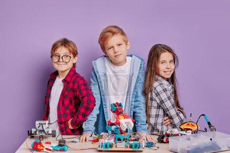 Photo pour Portrait attrayant d'enfants caucasiens avec la robotique sur la table, regarder la caméra et sourire. de futurs ingénieurs, des enfants surdoués - image libre de droit