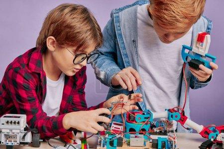 Photo pour Close-up portrait of boys diligently assembling robots, careful kids connectng wires of robot toys. future engineers boys - image libre de droit