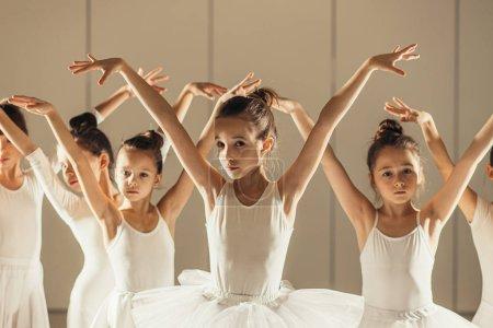 Photo pour Groupe de petites ballerines caucasiennes debout dans une rangée et pratiquer le ballet ensemble. assez étonnants danseurs en studio - image libre de droit