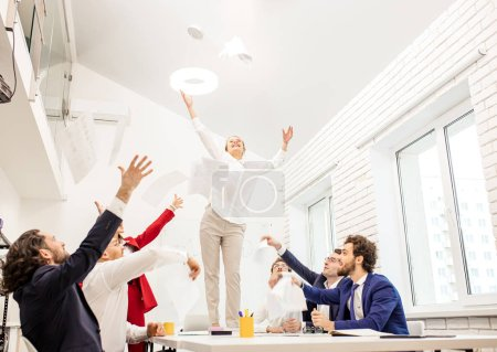 Photo pour Happy positive business team in office, young happy woman in white formal wear stand on table after successful completion of their business project - image libre de droit