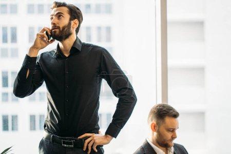 Photo pour Homme occupé en chemise noire officielle parler au téléphone avec des partenaires d'affaires pendant la conférence au bureau, collègue en tux assis à côté de la fenêtre panoramique à l'arrière-plan - image libre de droit