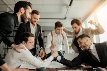 Photo pour Des chefs d'entreprise jouant au bureau après le travail, portant des vêtements officiels. Une équipe d'hommes d'affaires enthousiastes et actifs se réunit - image libre de droit