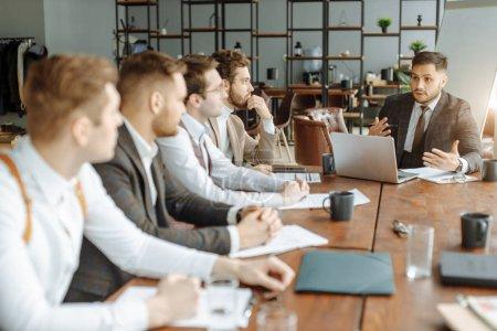 Foto de Hombres caucásicos ocupados en esmoquin sentarse en la mesa en la oficina escuchando al jefe y tomar notas en el cuaderno, escuchar atentamente los consejos y estrategias para el trabajo futuro por el líder - Imagen libre de derechos