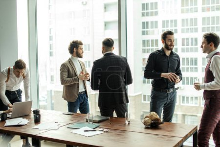 """Photo pour De jeunes gens d'affaires caucasiens, de beaux gars en tux élégant et élégant à la réunion, tenir une conférence pour discuter de nouveau projet de démarrage d'entreprise. Le succès dépend du travail d """"équipe et de la cohésion - image libre de droit"""