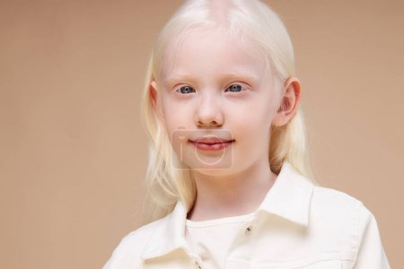 Portrait of smiling albino child girl isolated over beige background, unusual interesting appearance of girl is mesmerizing, natural beauty concept