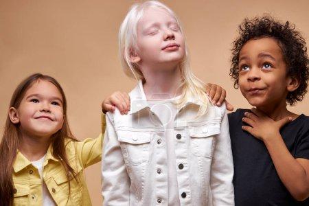 Photo pour Adorables enfants de diverses nationalités et couleurs de peau se tiennent ensemble posant à la caméra, groupe émotionnel d'enfants. albinisme, diversité des personnes, concept enfant - image libre de droit