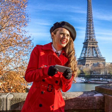 happy trendy woman on embankment in Paris, France writing sms