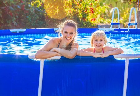 Photo for Fun weekend alfresco. Portrait of happy active mother and child in swimsuit in the swimming pool relaxing - Royalty Free Image