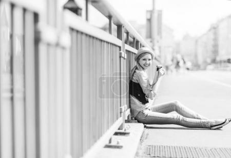 Young hipster sitting on city street with retro photo camera