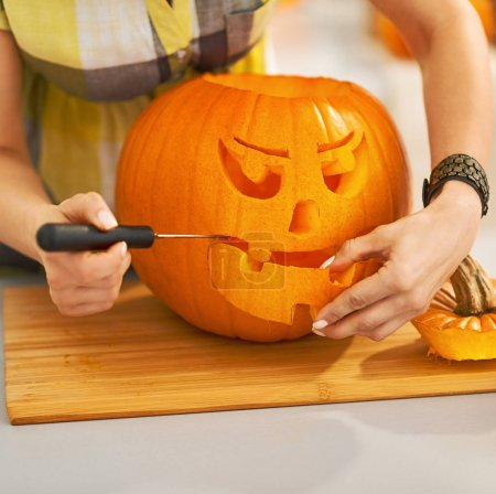 Frightful Treats on the way. Closeup on housewife in the Halloween decorated kitchen carving a big orange pumpkin