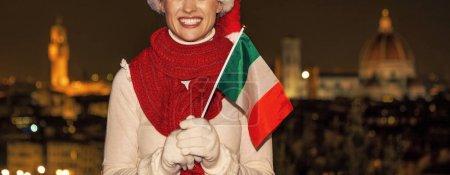 Photo pour Voyage plein d'inspiration au temps de Noël à Florence. Gros plan sur une jeune femme souriante en chapeau de Noël à Florence, Italie avec drapeau italien - image libre de droit
