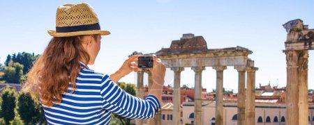 Photo pour Vacances romaines. femme touristique moderne à l'avant du Forum romain à Rome, Italie avec appareil photo numérique prenant des photos - image libre de droit