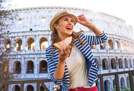 Vacaciones en Roma. mujer turista moda feliz en Roma, Italia con una rebanada de pizza mirando en la distancia