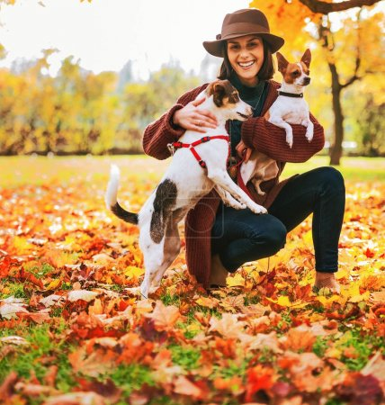Young woman in brown hat with two little dogs play...