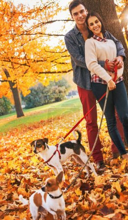 young couple with two little dogs on walk in park on autumn day