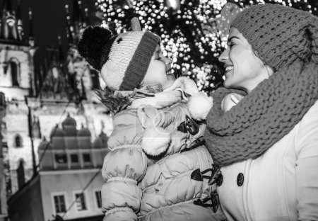 Magic on streets of the old town at Christmas. happy modern mother and daughter tourists at Christmas in Prague Czech Republic looking at each other