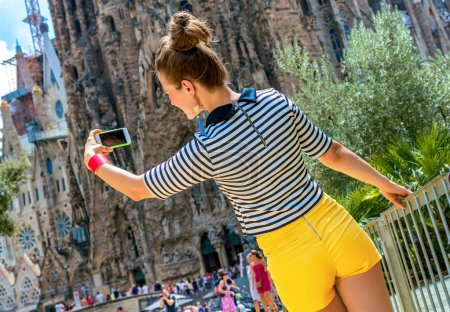 Barcelona - July, 10, 2017: Portrait of relaxed stylish tourist woman in yellow shorts and stripy shirt near Sagrada Familia in Barcelona, Spain
