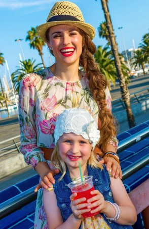 Photo pour Jeune mère souriante et les enfants voyageurs sur le remblai à Barcelone, Espagne avec boisson rouge vif - image libre de droit