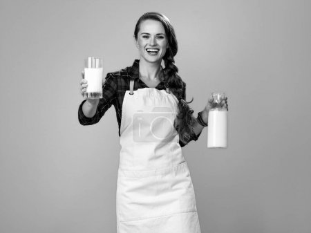 Portrait of smiling modern woman cook wearing apron giving glass of homemade fresh raw milk
