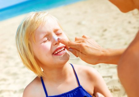 Sun kissed beauty. happy young mother and daughter in swimsuit on the beach applying SPF