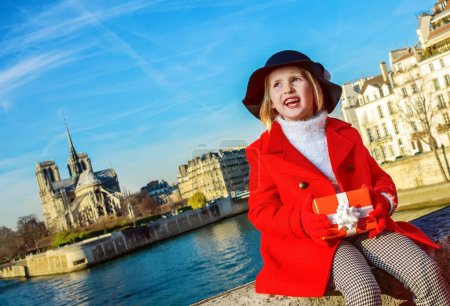 Photo pour Lumineux à Paris. joyeuse fille tendance en manteau rouge sur le remblai près de Notre Dame de Paris à Paris, France avec boîte cadeau de Noël regardant au loin - image libre de droit