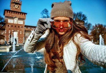 modern tourist woman near Sforza Castle in Milan, Italy taking selfie