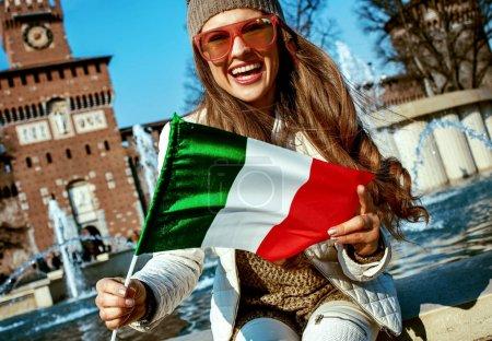Photo pour Heureuse jeune touriste près du château de Sforza à Milan, Italie montrant le drapeau - image libre de droit