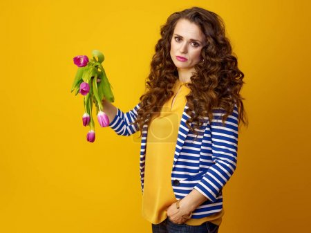 Photo for Unhappy trendy woman in striped jacket against yellow background showing wilted flowers - Royalty Free Image