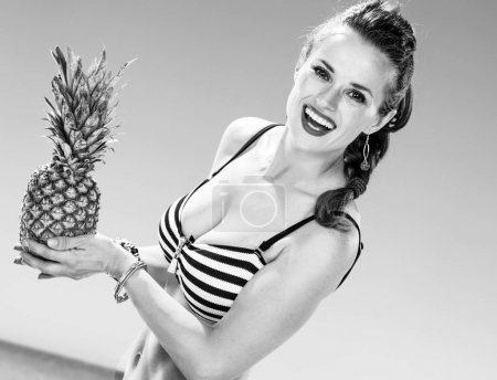 Perfect summer. happy woman in swimwear on the seashore holding pineapple