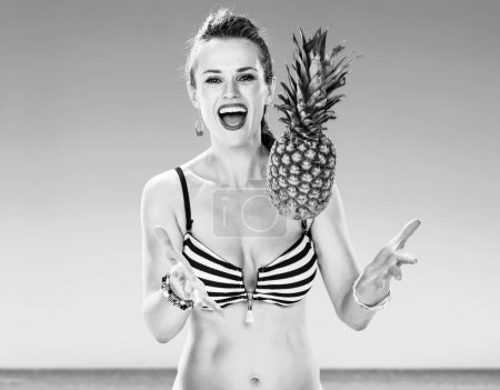 Perfect summer. smiling young woman in swimwear on the seacoast throwing pineapple up