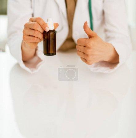 Photo pour Gros plan sur médecin femme montrant bouteille de médicament et pouces vers le haut - image libre de droit