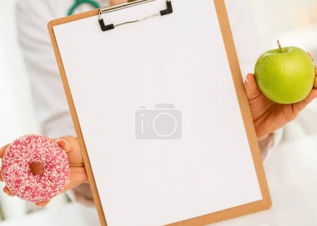 Closeup on medical doctor woman showing blank clipboard apple and donut