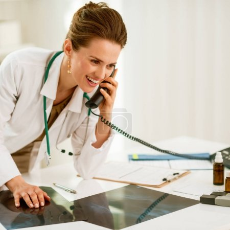Happy medical doctor woman with fluorography talking phone in office