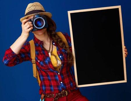 Photo pour Voyageur sain femme dans une chemise à carreaux avec tableau noir et appareil photo numérique prenant des photos - image libre de droit