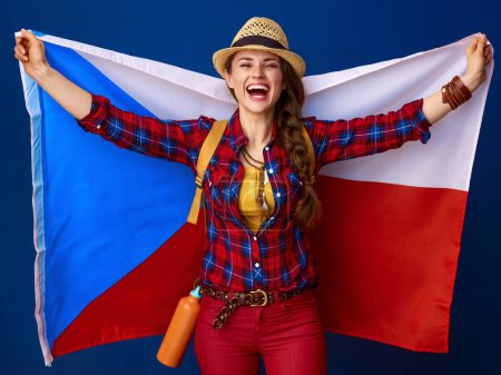 smiling active woman hiker in a plaid shirt holding flag of Czech on blue background