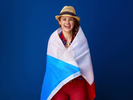 happy healthy woman hiker with backpack wrapped up in flag of Czech isolated on blue background