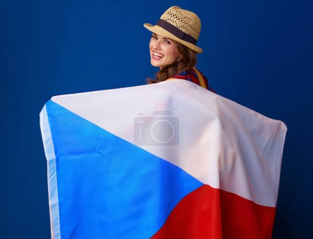 Seen from behind active woman hiker in a plaid shirt holding the flag of Czech on blue background